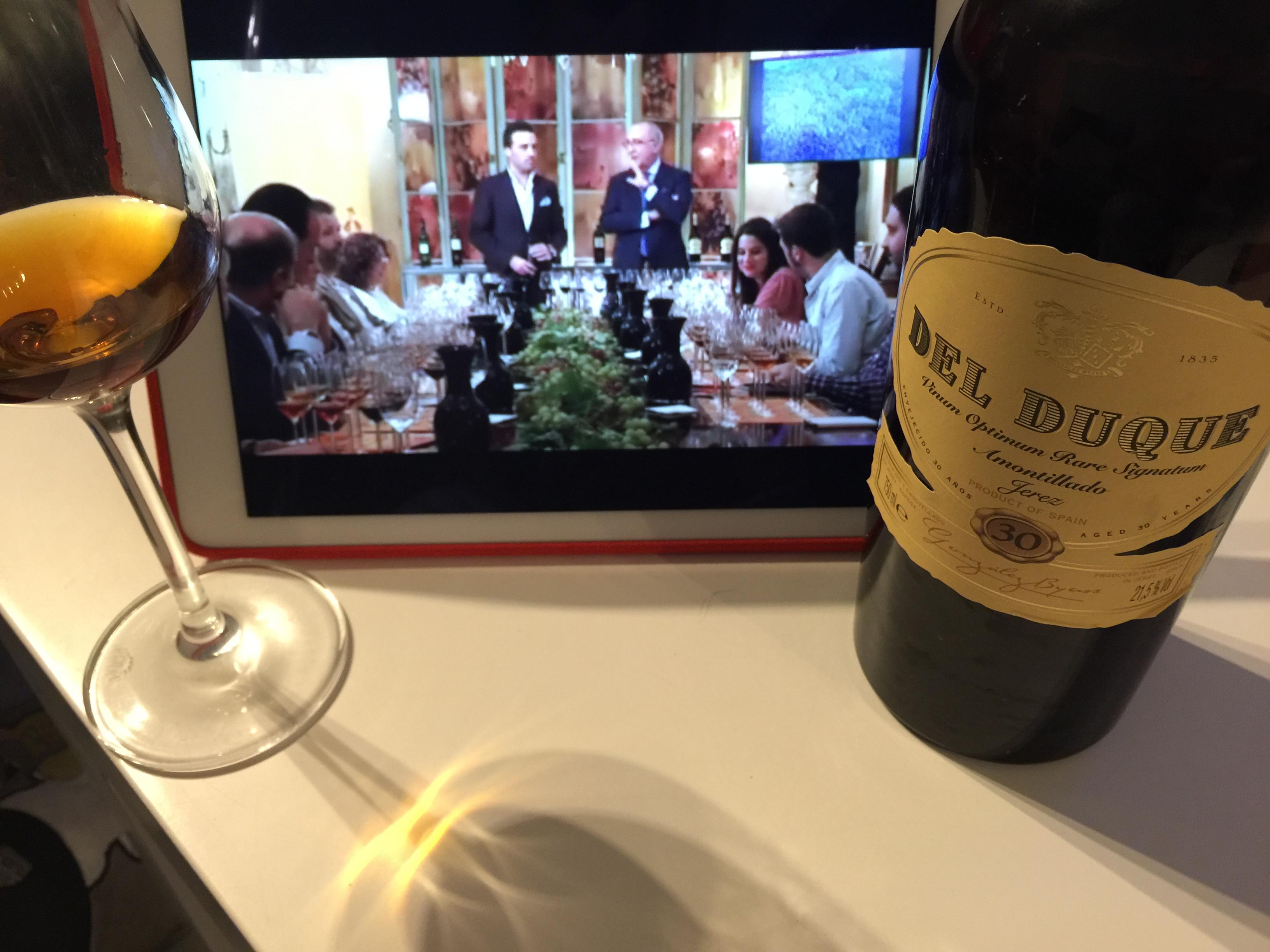 Imagen de una copa de amontillado Del Duque junto a su botella y un iPad en el que se ve un cata virtual de Antonio Flores, enólogo de González Byass