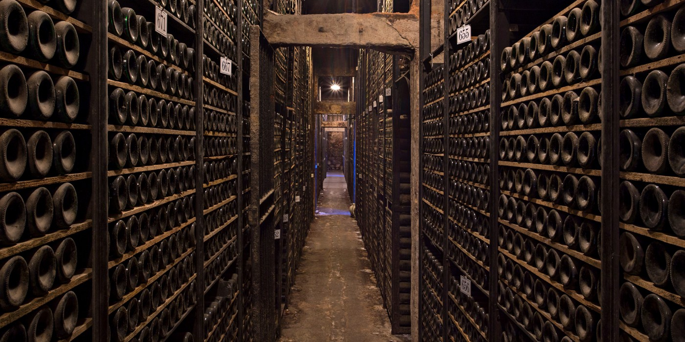Pasillo estrecho con las paredes repletas de botellas viejas de vino.